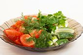 picture of cucumber slice  - Tomatoes and cucumbers sliced in a brown dish on a white background - JPG