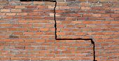 stock photo of foundation  - Large crack in a brick wall building foundation - JPG
