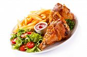 stock photo of thighs  - Grilled turkey thighs with chips and vegetables  - JPG