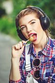 picture of lollipop  - Portrait of a young attractive girl hipster headphones gnawing lollipop - JPG