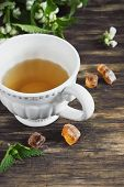 stock photo of nettle  - nettle tea and twigs of fresh nettle on the old wooden background - JPG
