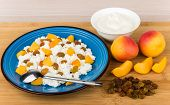 stock photo of curd  - Grainy curd with peaches and raisins bowl with sour cream on bamboo board - JPG