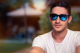 stock photo of swagger  - Portrait of a handsome with sport style sunglasses with mirror lenses - JPG