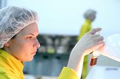stock photo of pharmaceutical company  - Lab technician inspecting the quality of glass ampoules at a pharmaceutical factory - JPG