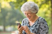 Smiling elderly woman with spectacles and typing phone message while sitting at park. Senior woman u poster