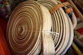 picture of firehose  - Antique Fire Hose rolled up on display in Fire Museum - JPG