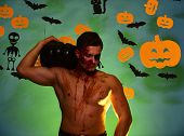 Man With Smiling Face And Sexy Naked Torso Stands On Green Background. Macho With Torso, Pumpkins An poster