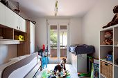 Child bedroom with many games on the ground. Nobody inside poster