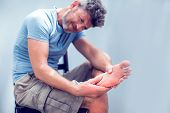 Pain In The Foot, Man Holds Hands To His Feet, Foot Massage, Cramp, Muscular Spasm, Red Accent On Th poster