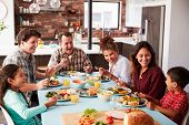 Multi Generation Family Enjoying Meal Around Table At Home Together poster