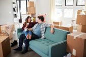 Happy Couple Resting On Sofa Surrounded By Boxes In New Home On Moving Day poster