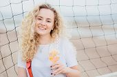 Optimistic Young Female Model With Curly Light Hair, Dressed In Casual White T Shirt, Drinks Fresh C poster