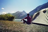 Alone Man Travel Near The Lake Mountain Background, Travel Alone Concept. Young Tourist Guy Sitting  poster