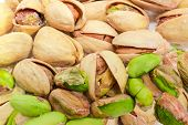 Background Of The Roasted Salted Pistachio Nuts Peeled From Shells And Nuts With Partly Open Shells  poster