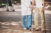 Doctor Helping Old Man Patient With Crutches. Care For Elderly People Concept. Concepts Of Health Ca poster
