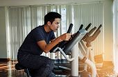 Muscular Young Asian Man Exercising His Legs Cardio Training On Bicycle In Fitness Gym For Good Heal poster