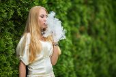 Vape Teenager. A Young Cute White Girl In A Dress Is Vaping An Electronic Cigarette Between Thuja On poster