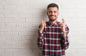 Young adult man standing over white brick wall smiling crossing fingers with hope and eyes closed. L poster