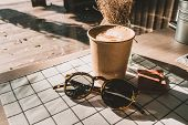 Cappuccino In Take Away Coffee Cup And Sunglasses On Table Cloth With Dry Flower On Wood Table With  poster