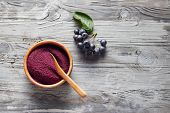 Organic Aronia powder in a bowl with fresh aronia berries on table.  poster