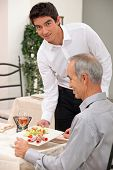 Young waiter serving an older customer