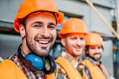 Close-up Shot Of Group Of Equipped Builders Looking At Camera At Construction Site poster