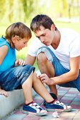 stock photo of scabs  - Dad helping boy to wipe blood off his injured leg - JPG