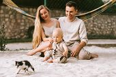 Happy Family With Little Son And Kitten Sitting On Sand With Hammock Behind At Countryside poster