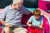 An Elderly Man And His Young Grandson Ride A Carnival Ride At A Theme Park.  The White Haired Man Lo poster