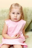 Little Child A Girl In Pink Dress Sitting On Sofa In Domestic Room. poster