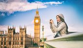 London europe travel woman taking pictures with phone. Mobile photography. Tourist holding smartphon poster