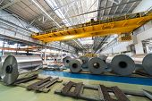 Rolls of aluminum and crane in production shop of plant in special places.