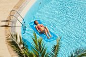 Young woman in red swimsuit sunbathes lying on inflatable mattress on water near to edge of pool