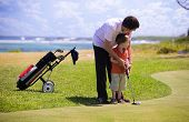 stock photo of golf  - Father teaching his son how to play golf - JPG