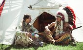 stock photo of indian chief  - North American Indians sit at a wigwam - JPG