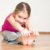 stock photo of tilt  - smiling little girl in pink engaged in fitness - JPG