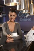 stock photo of bartender  - Portrait of attractive female bartender handing coffee cup towards camera - JPG