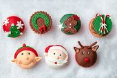 Seasonal festive Christmas mini dessert cupcakes in traditional decorative symbols elements