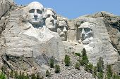stock photo of rock carving  - Scuptured faces of the Presidents George Washington Thomas Jefferson Theodore Roosevelt and Abraham Lincoln carved into a mountain in - JPG