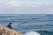 stock photo of fly rod  - fisherman with a fishing rod on sea - JPG