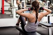 stock photo of outfits  - Pretty brunette doing crunches in front of a mirror in a gym - JPG