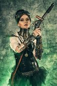 stock photo of post-apocalypse  - Portrait of a beautiful steampunk woman holding a gun over grunge background - JPG