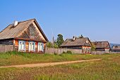 foto of siberia  - Row of traditional wooden houses in a remote village in Russian Siberia at the shores of Lake Baikal - JPG
