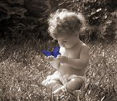 pic of cute baby  - sepia photo of baby intrigued by a blue tinted butterfly - JPG