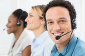 stock photo of helping others  - Happy Customer With Headsets Working With Other Colleague In Call Center - JPG