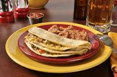 stock photo of shredded cheese  - Shredded beef and cheese quesadillas with refried beans and beer - JPG
