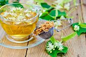picture of lime-blossom  - Metal sieve with dried flowers of lime fresh flowers linden tea in glass cup on the background of wooden boards - JPG