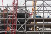 foto of construction crane  - Construction site of a new building of steel and concrete floors - JPG