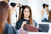 Постер, плакат: Reflection of hairdresser doing haircut for woman in hairdressing salon Concept of fashion and beau