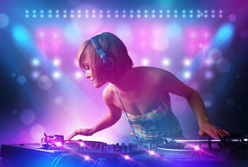 image of disc jockey  - Pretty young disc jockey mixing music on turntables on stage with lights and stroboscopes - JPG